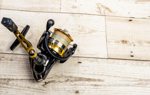 Golden Fishing Reel On Wooden ...