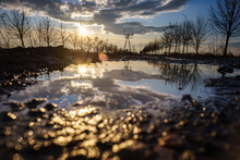 HDR Photo Of The Setting Sun Reflecting In A Puddle.