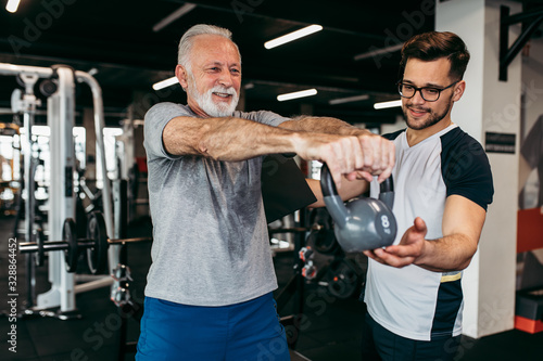 Foto Senior man exercising in gym with his personal trainer.