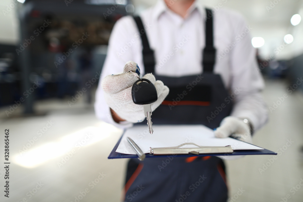 Fototapeta Close-up view of service station worker returning keys to owner and filling clipboard paper. Car maintenance concept. Skilled professional mechanic in garage