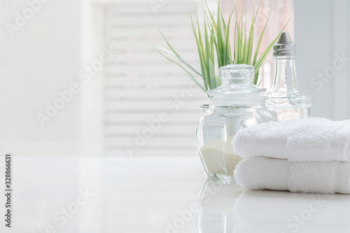 White folded towels and glass bottle on white table with copy space on blurred bathroom background Fototapet