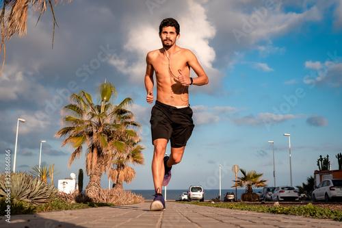 joven  con el torso desnudo sale a correr a la calle a última hora de la tarde Wallpaper Mural