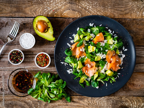Photo Salmon salad - smoked salmon white rice and vegetables on wooden table