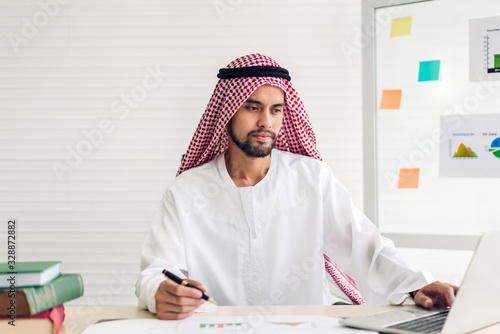 Photo Handsome confident arab businessman working and looking at technology of laptop computer monitor