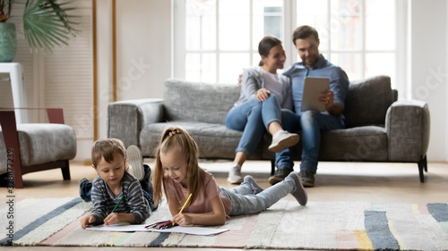 Obraz Full length small playful boy lying on floor carpet with happy elder sister, drawing pictures in paper album, while smiling parents resting on sofa, using digital tablet, watching funny videos. - fototapety do salonu