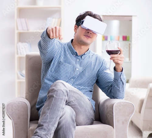 Obraz Young man drinking wine at home - fototapety do salonu