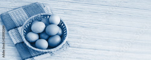 Real farm chicken eggs lie in a wicker basket on the table Wallpaper Mural