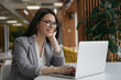 Businesswoman using laptop computer, watching training courses. Portrait of happy successful manager working in office. Beautiful woman freelancer wearing stylish eyeglasses sitting at workplace