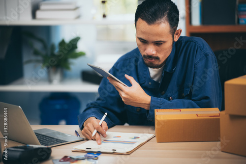 Young man entrepreneur selling online product sitting smile happily in him workplace.