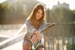Attractive tempting young girl in fashion jeans clothes wears stylish glasses ,sitting on the bicycle and posing on camera at summer evening. Slow motion