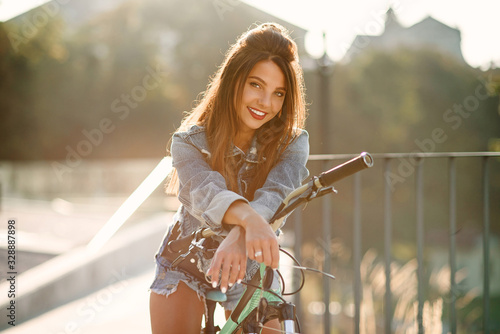 Obraz Attractive tempting young girl in fashion jeans clothes wears stylish glasses ,sitting on the bicycle and posing on camera at summer evening. Slow motion - fototapety do salonu