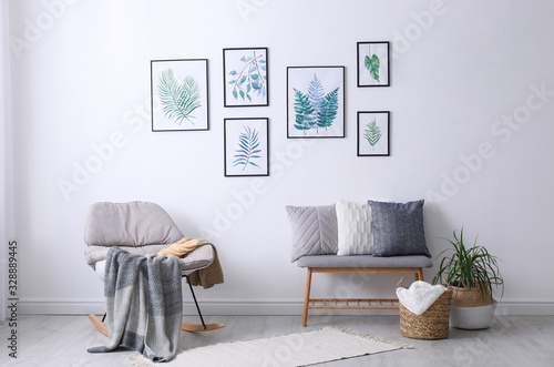 Fototapety, obrazy: Beautiful paintings of tropical leaves on white wall in living room interior