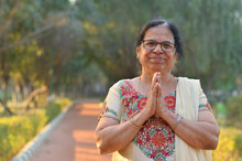 Smart Senior North Indian Woman Standing, Posing For The Camera With Hands Folded In Namaste As A Sign Of Respect And Welcome In A Park Wearing Off White Salwar Kameez In Summers In New Delhi, India