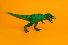 Green Dinosaur Toy With Open Mouth On A Vivid Orange Background