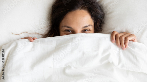 Fotomural Close up top view portrait of smiling Caucasian young woman lying in white comfo