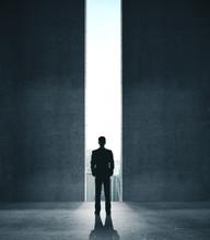 Businessman In Concrete Room With Open Door To City