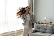 Overjoyed Millennial Girl Wearing Headphones Have Fun Moving Listening To Music Relax In Living Room, Happy Young Woman In Earphones Dance Enjoy Leisure Weekend At Home, Stress Free Concept