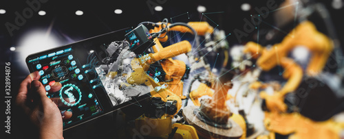 Engineer hand using digital tablet and checking welding robotics automatic arms machine Canvas Print