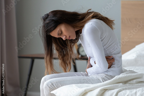 Sick young woman sit on bed at home touch belly suffer from stomach ache, stressed ill millennial girl feel bad struggle with periods pain, having indigestion, eating disorder, health problem concept