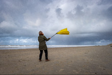 Woman Struggling With Big Yellow Umbrella On Beach In Stormy Weather