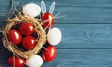 Colored Deep Red Easter Eggs In Nest Top View Background, Selective Focus Image. Happy Easter Card