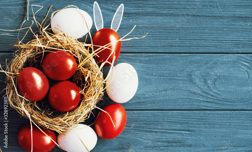 Stampa su Tela colored deep red Easter eggs in nest top view background, selective focus image
