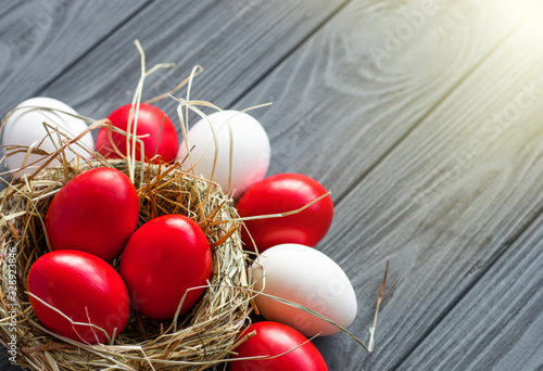 Carta da parati colored deep red Easter eggs in nest top view background, selective focus image
