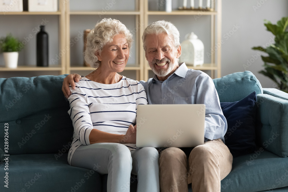 Fototapeta Overjoyed Caucasian old 60s couple sit relax on sofa in living room laugh watching funny video on laptop, happy elderly husband and wife cuddle rest on couch using modern computer at home together