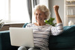 Overjoyed elderly 60s woman sit relax on couch in living room feel excited winning lottery online on computer, happy old 50s grandmother rest at home triumph reading good news on Internet on laptop