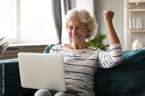 Photo Overjoyed elderly 60s woman sit relax on couch in living room feel excited winni