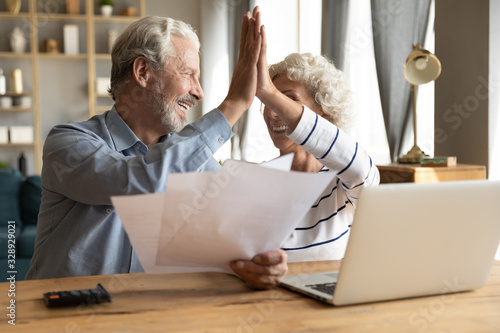 Happy old 60s couple spouses sit at desk at home give high five celebrate good news in letter document, smiling elderly husband and wife pay bills on internet on laptop online, easy banking system
