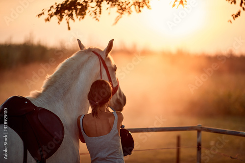 Young rider girl with her horse at sunset.