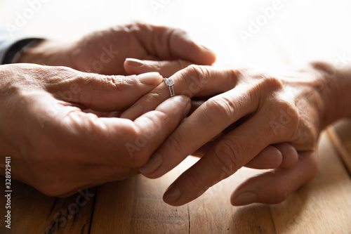 Photo Close up view of old 60s man put wedding engagement ring on beloved woman hand f