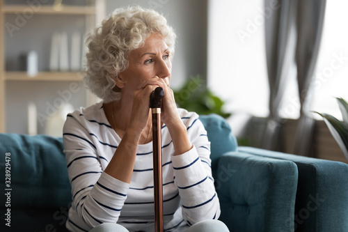Pensive disabled old lady sit on couch in living room look in window distance th Fototapet