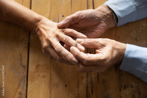 Top close up view of old mature man put wedding ring on middle-aged 50s woman ha Wallpaper Mural