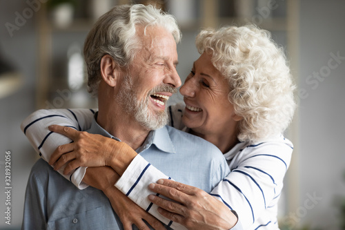 Photo Happy elderly retired 60s husband and wife hug cuddle look in eyes share close t