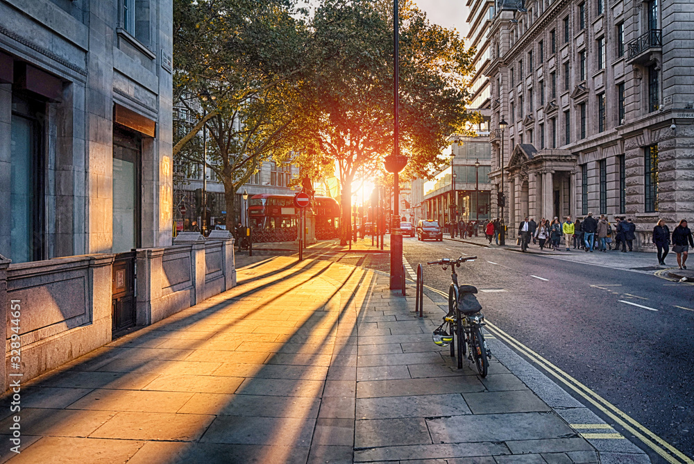 Fototapeta Looking towards the setting sun on Pall Mall East with bus, taxi, bicycle and people with blurred faces
