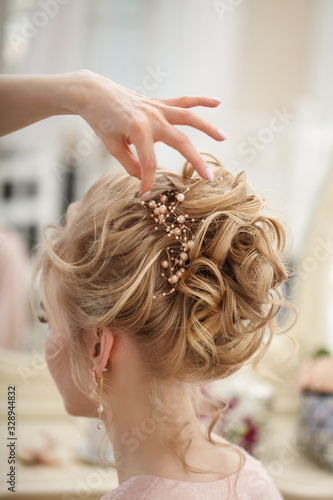Foto Makeup artist, hair professional stylist makes young beautiful bride bridal make