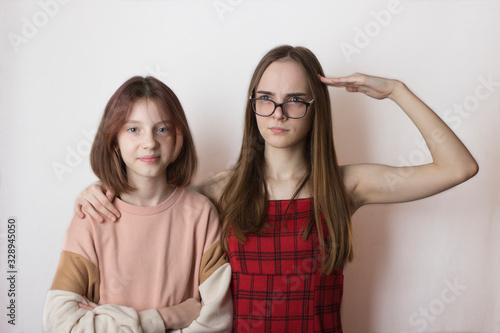 Photo stepsisters or friends children teens not like each other on a white background