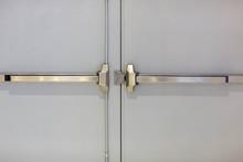 Emergency Fire Exit Door. Closed Up Latch And Rusty Door Handle Of Emergency Exit. Push Bar And Rail For Panic Exit. Open One Way Door.  Steel Of Handle For The White Door Fire Exit