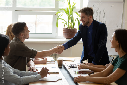 Happy male colleagues shake hands get acquainted greeting at team meeting in off Wallpaper Mural