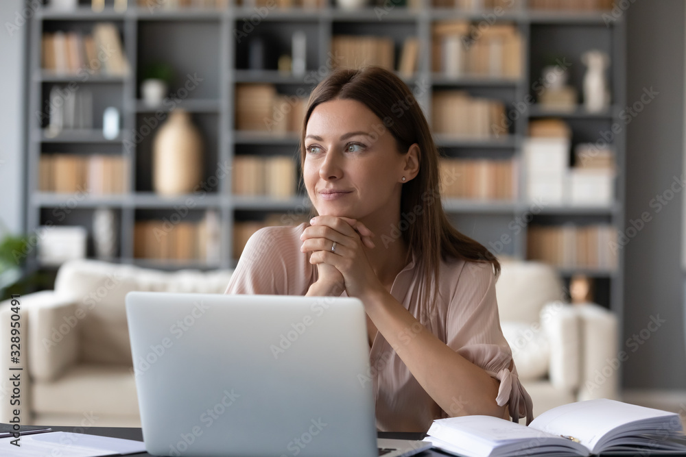 Fototapeta Head shot young dreamy woman sitting at table, distracted from computer work. Lost in thoughts lady looking away, planning visualizing future at home. Entrepreneur enjoying break pause time.