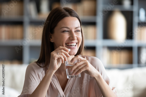 Photo Head shot smiling young woman holding pill and glass of fresh pure water