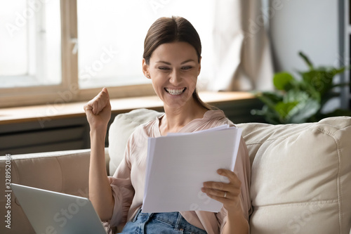 Excited young woman reading paper documents, making yes gesture Canvas Print