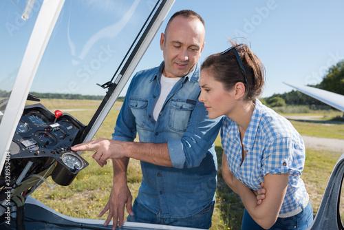 man showing woman the controls of a sailplane Tapéta, Fotótapéta