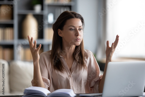 Photo Unhappy young woman looking at laptop screen, irritated by bad gadget work, low internet connection, working remotely at home