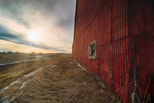 Stunning Dramatic Sunsets In Rural Farm Country With Barns And Cold Fields With Rainbow.
