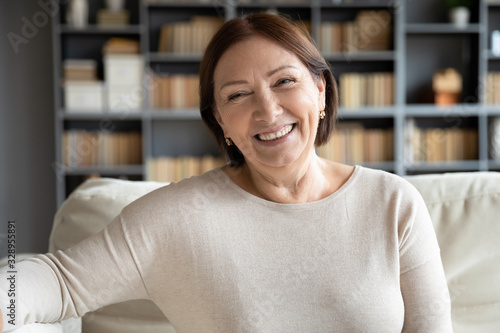 Fotomural Head shot close up portrait happy healthy middle aged woman sitting on comfortable couch at home