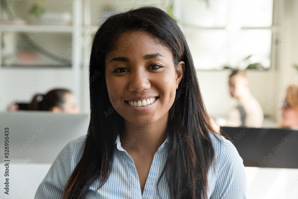 Fototapeta Headshot portrait of smiling African American female employee have video call or web conference in office, profile picture of happy biracial woman worker posing look at camera in coworking space