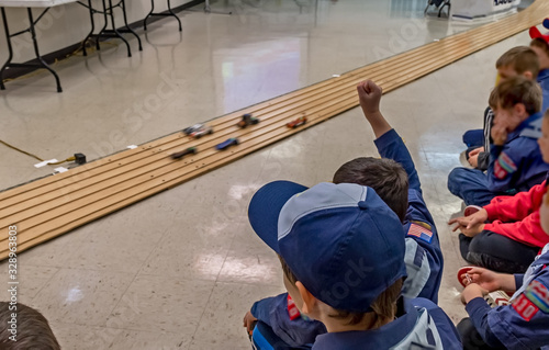 Canvas Print Excited cub scout boys at pinewood derby car race